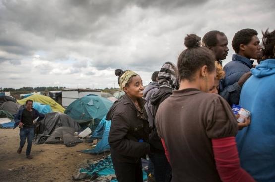 Een vrouw schuift aan bij de verdeling van hulpgoederen in Calais. (Foto Evy Menschaert)