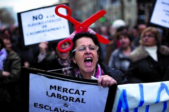 Een vrouw vergelijkt de arbeidsmarkt met slavernij tijdens een betoging tegen arbeidsmarkther- vormingen van de Spaanse regering in februari 2012 in Barcelona. (Foto AP/ Emilio Morenatti)