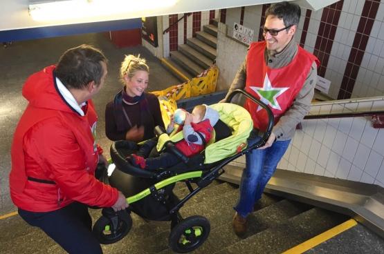 PVDA Hasselt helpt jonge ouders met kinderwagen, zwaarbepakte reizigers en ouderen de trap op in het station van Hasselt, waar de hoofdroltrap lange tijd kapot was. (Foto PVDA Limburg)