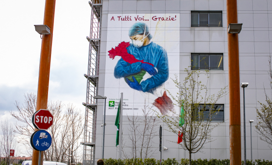De Italiaanse ziekenhuizen kunnen het aantal coronaviruspatiënten niet aan... maar ze hebben de volledige steun van de bevolking, zoals dit gigantische fresco in Bergamo laat zien. (Foto Belga, Sergio Agazzi)