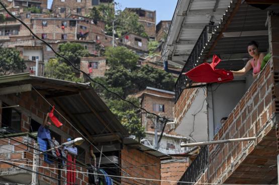 Bewoners van de Colom biaanse stad Medellin besloten uit protest een rode vlag aan hun raam te hangen, omdat de overheid niets voor hen doet. (Foto Joaquin Sarmiento, AFP)