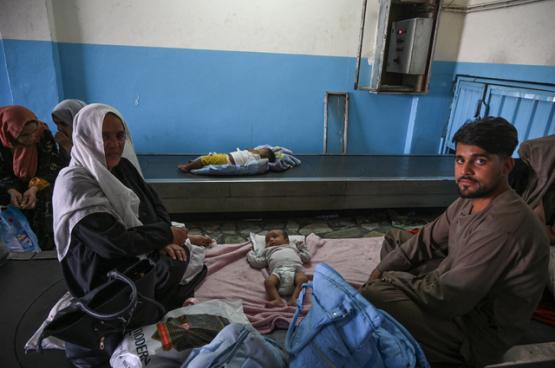 Een Afghaans koppel ververst de luiers van hun baby in de luchthaven. Het resultaat van Westerse inmenging. (Foto Belga)